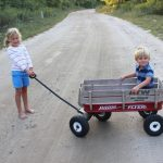 Stella Schafer pulls her brother Sam along a sandy path.